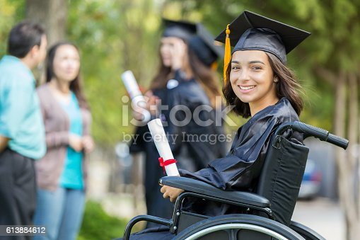 istock Cheerful young Hispanic woman holds college diploma 613884612