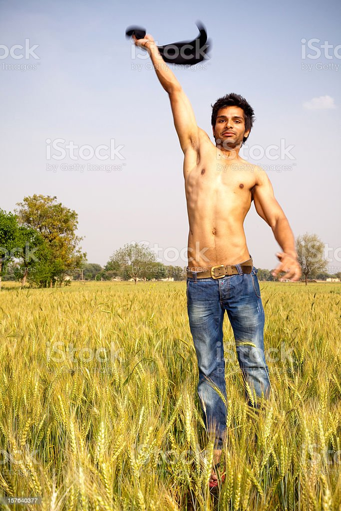 Cheerful Young Indian Adult Jumping in the Wheat Fields royalty-free stock photo