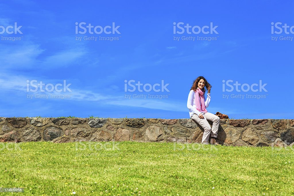 Cheerful young lady sitting on a wall against blue sky royalty-free stock photo