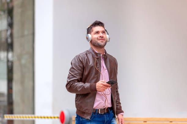 Ein fröhlicher, junger lateinamerikanischer Büroangestellter hört Musik mit einem Mobiltelefon und einem fortschrittlichen Headset, direkt vor einem Bürogebäude im Morgensonnenschein, während er zur Arbeit geht. – Foto