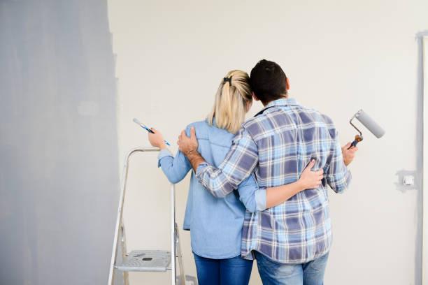 fröhliche junge liebespaar im neuen haus malen und dekorieren ihr heim wand - französisches haus dekor stock-fotos und bilder