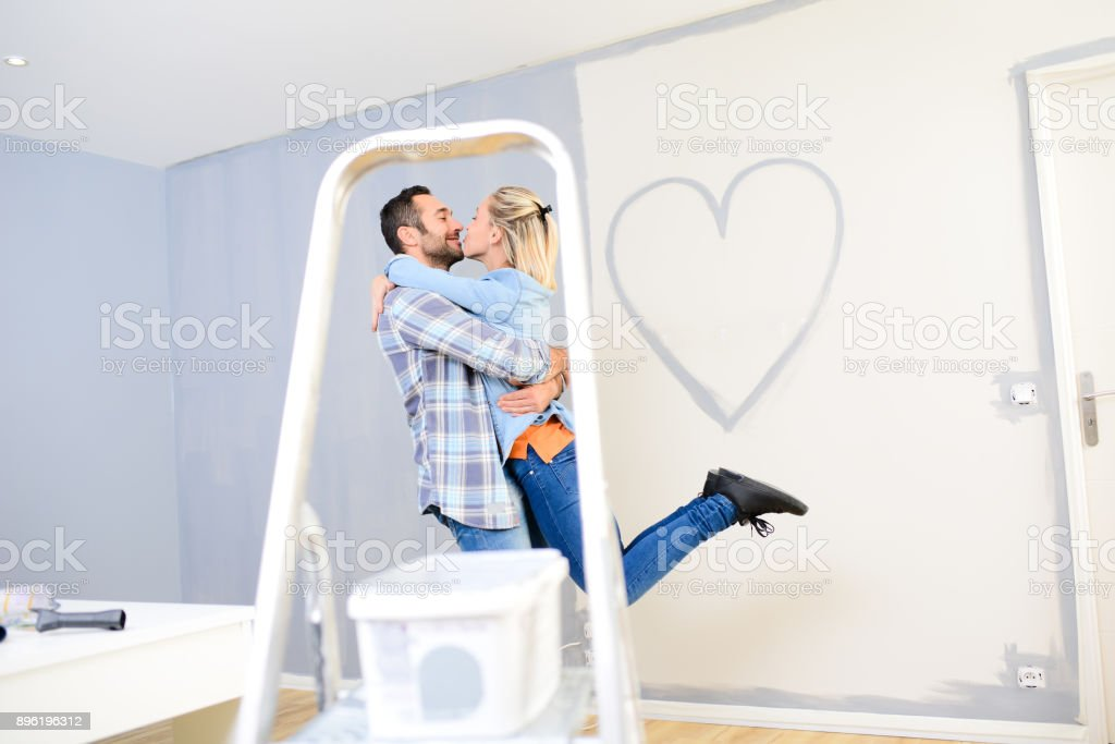 Cheerful Young Love Couple In New House Painting Decorating Home And