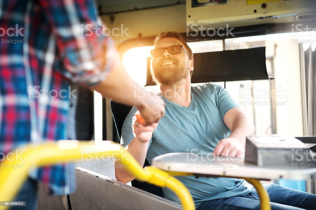 Cheerful young male bus driver is looking at the passenger and politely smiling while charging the ticket fee. stock photo