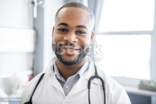 Young African medic in his 20s, smiling towards camera, head and shoulders portrait