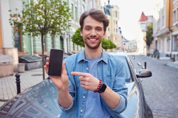 Cheerful young male showing his smartphone screen stock photo