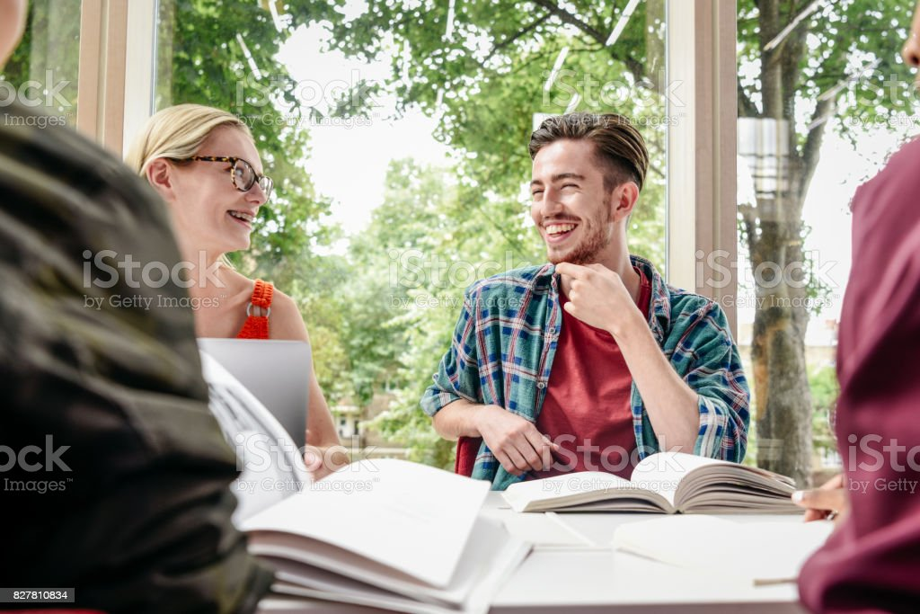 Cheerful young male student laughing with friends, text books on table stock photo