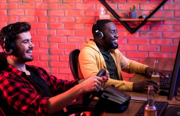 fröhliche junge männer erfreuen sich autorennen videospiel - steuerungstechnik stock-fotos und bilder