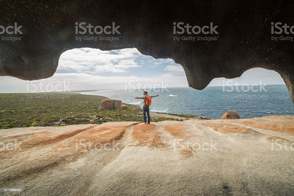 Cheerful young man arms outstretched at The Remarkable rocks-Australia stock photo
