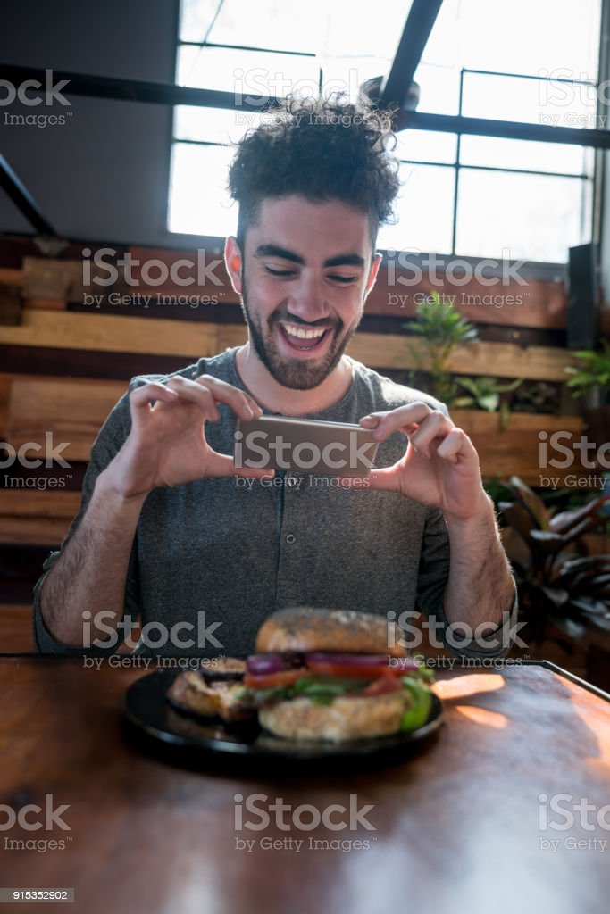 Cheerful young man at a vegetarian restaurant taking a photo of his dinner stock photo
