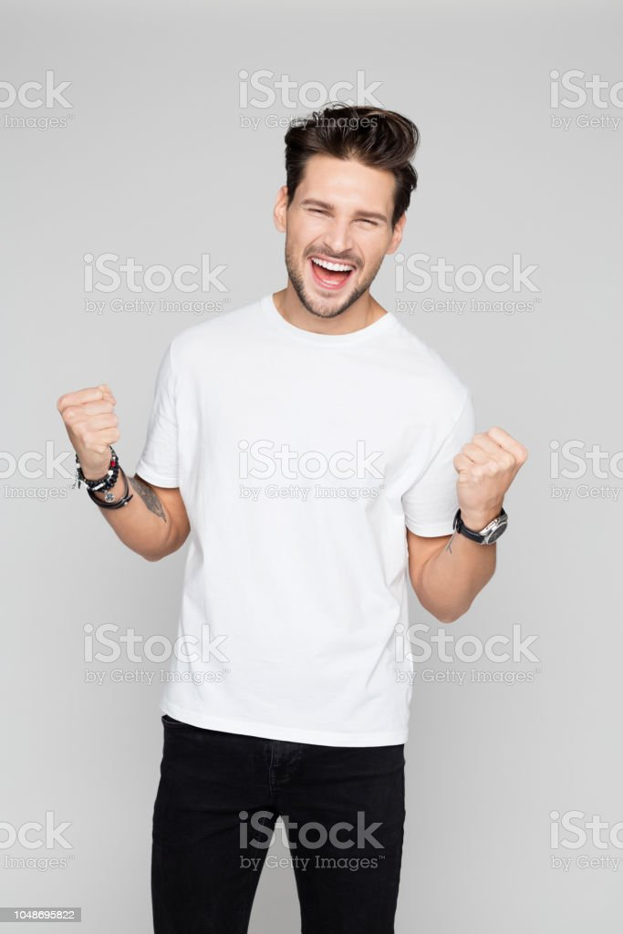 Cheerful young man celebrating success Portrait of cheerful young man celebrating success with clenched fist on grey background 25-29 Years Stock Photo