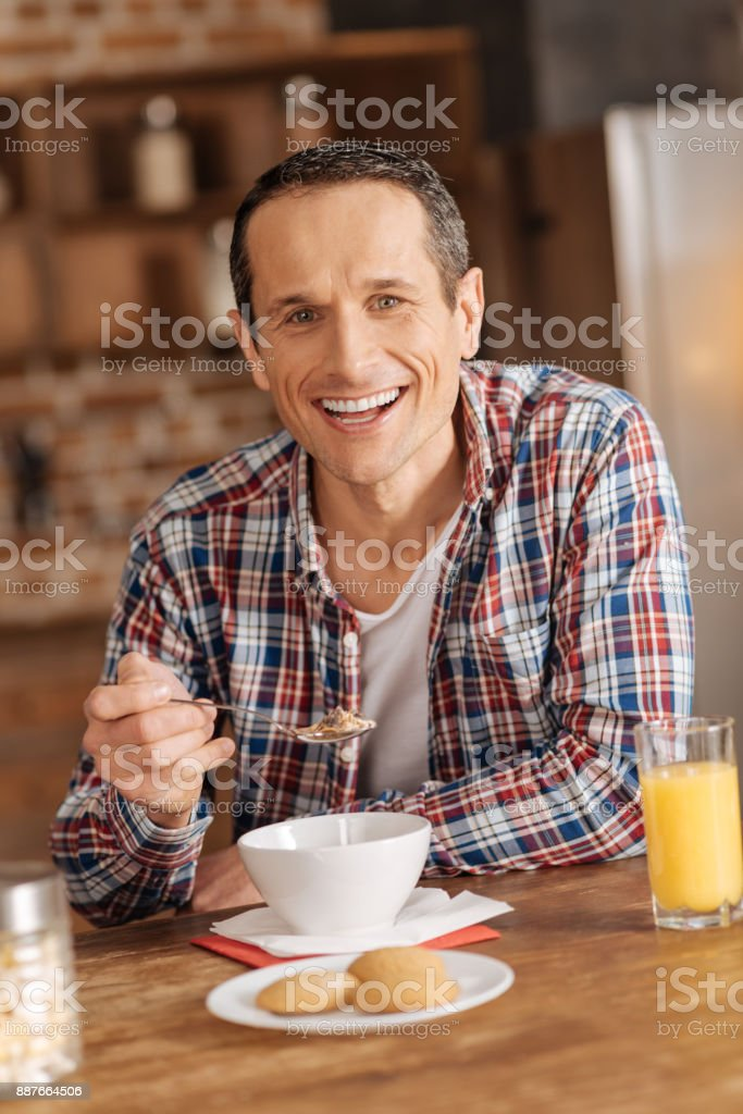 Cheerful young man eating cereals for breakfast stock photo
