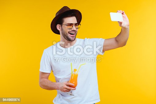 cheerful young man holding glass of summer cocktail and taking selfie with smartphone isolated on yellow