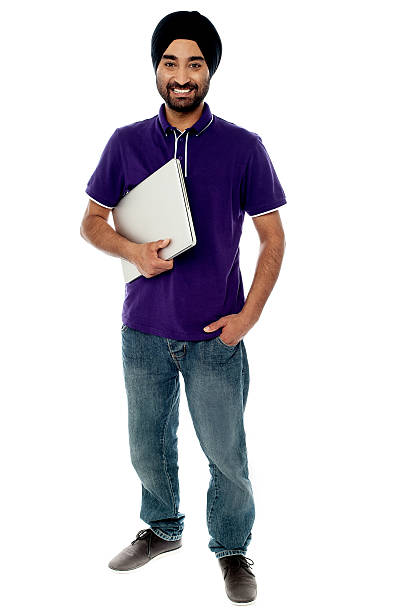 Cheerful young man holding laptop stock photo
