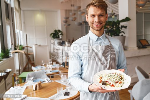 istock Cheerful young man holding plate of fresh salad 1225932892