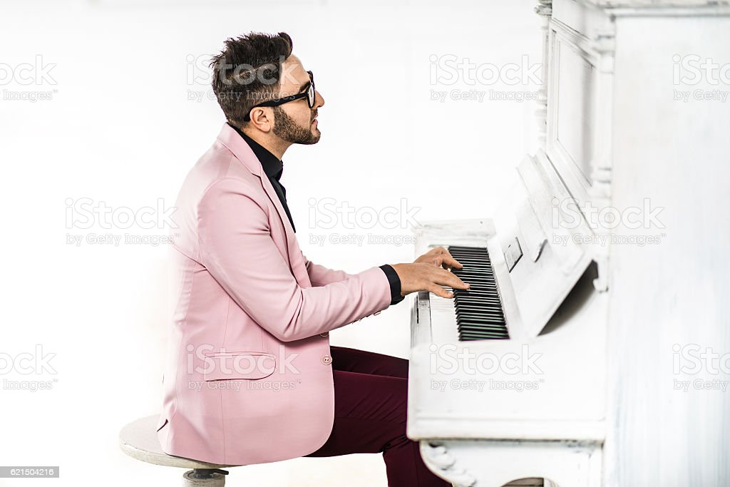 Cheerful young man in stylish suit is playing piano Lizenzfreies stock-foto