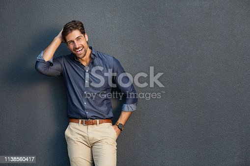 Portrait of smart business man standing and laughing against gray wall. Confident entrepreneur feeling excited on success and looking at camera. Young businessman in casual clothing smiling isolated on grey background with copy space.