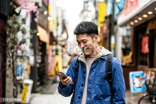 Young Chinese man in his 20s smiling and checking mobile phone, carrying backpack, city life, communication, social media