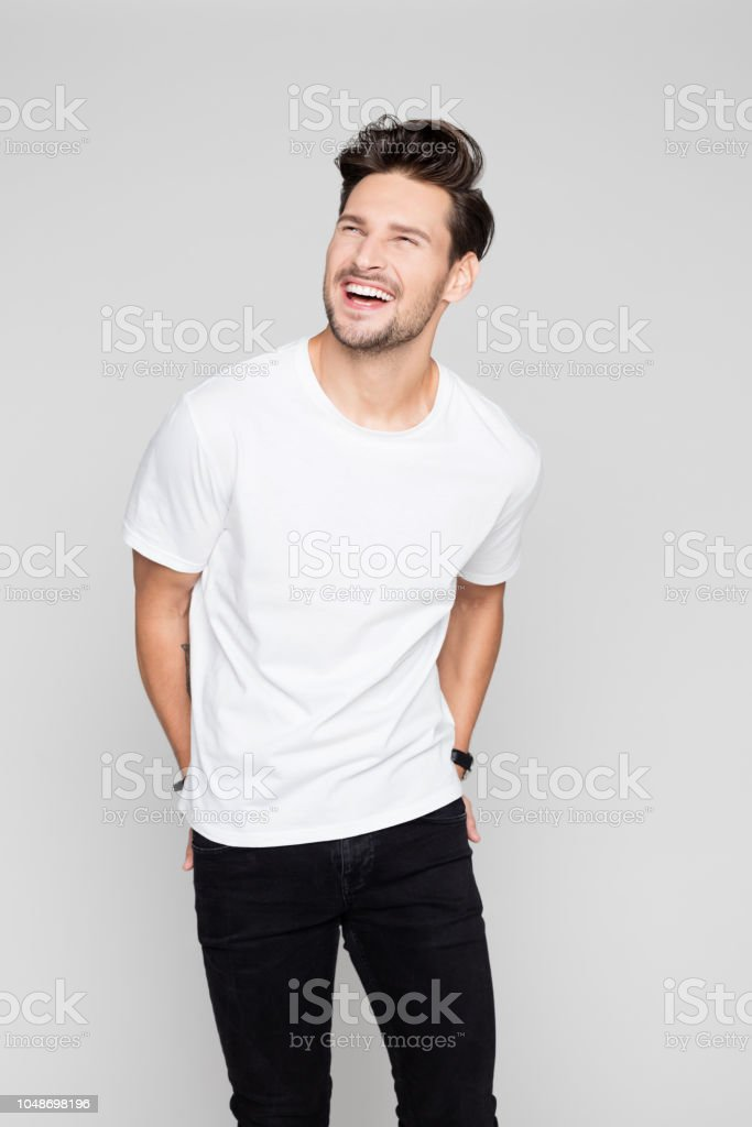 Cheerful young man looking away and laughing Portrait of cheerful young man looking away and laughing on grey background 25-29 Years Stock Photo