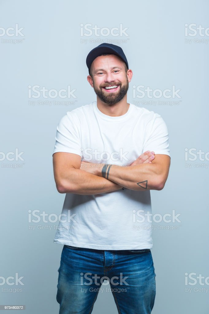 Cheerful young man looking relaxed Portrait of cheerful young man is casuals standing on white background with arms crossed Adult Stock Photo