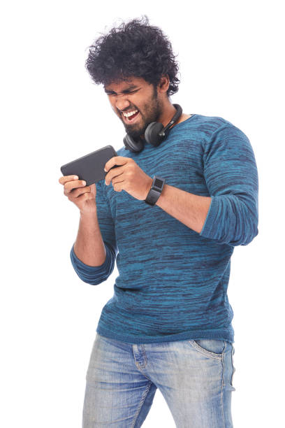 cheerful young man playing game with latest smart phone - mobile game stock photos and pictures