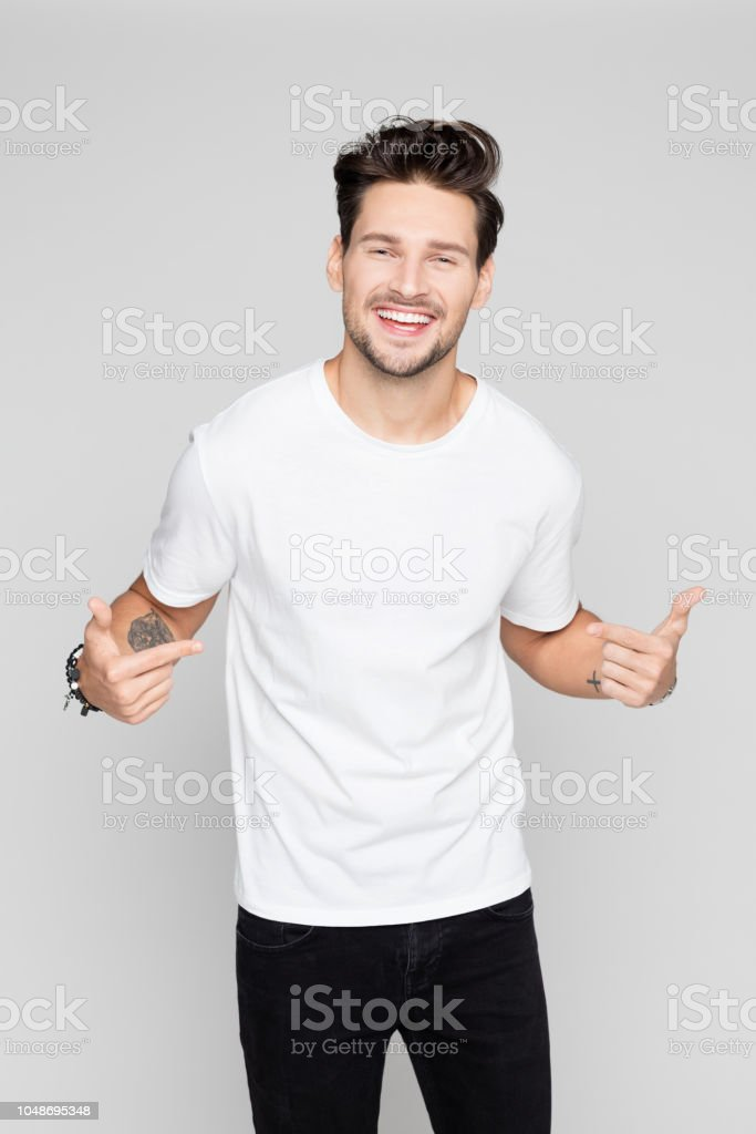 Cheerful young man pointing at himself Portrait of cheerful young man pointing at himself on grey background 25-29 Years Stock Photo