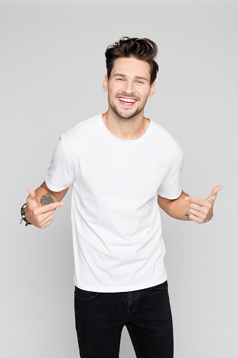 Cheerful young man pointing at himself
