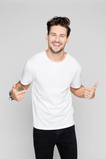 cheerful young man pointing at himself - white tshirt stock photos and pictures