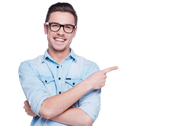 Cheerful young man pointing copy space. stock photo