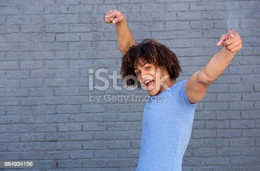 istock cheerful young man pointing fingers 664934156