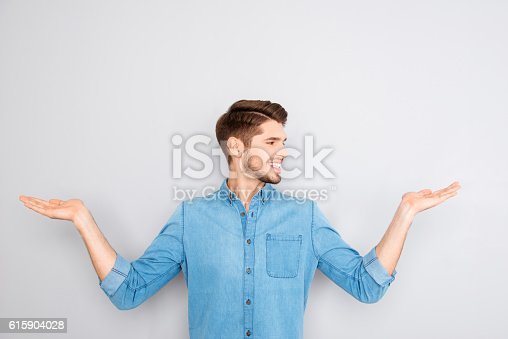 istock Cheerful young man presenting products in both hands 615904028