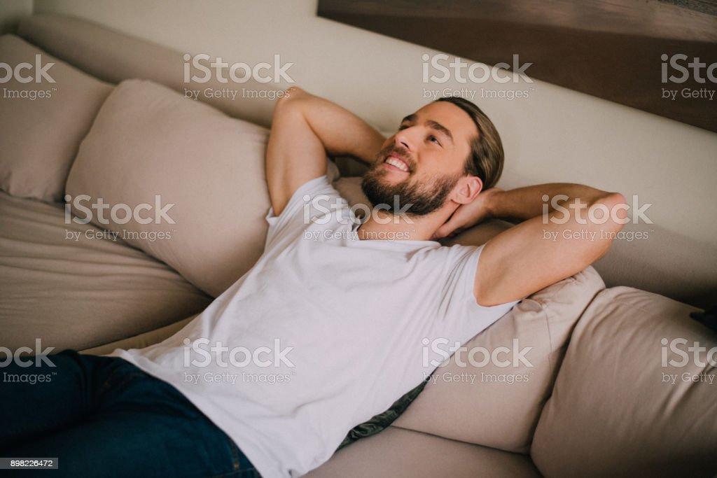 A cheerful young man resting on a sofa in his living room stock photo