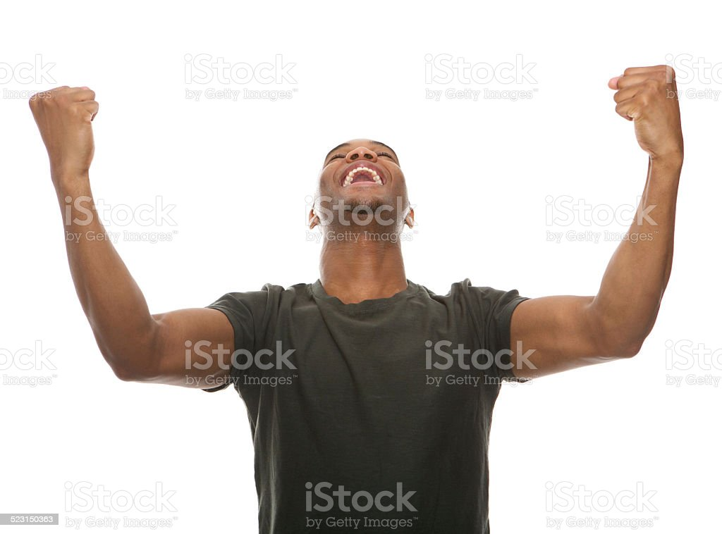 Cheerful young man shouting with arms raised in success stock photo
