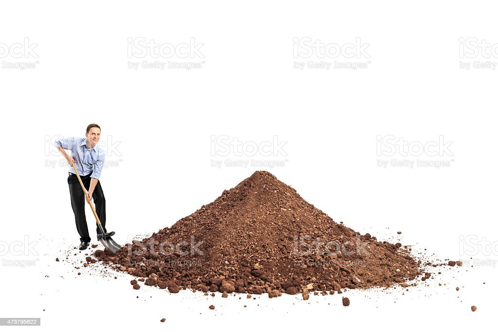 Cheerful young man shoveling a big pile of dirt stock photo