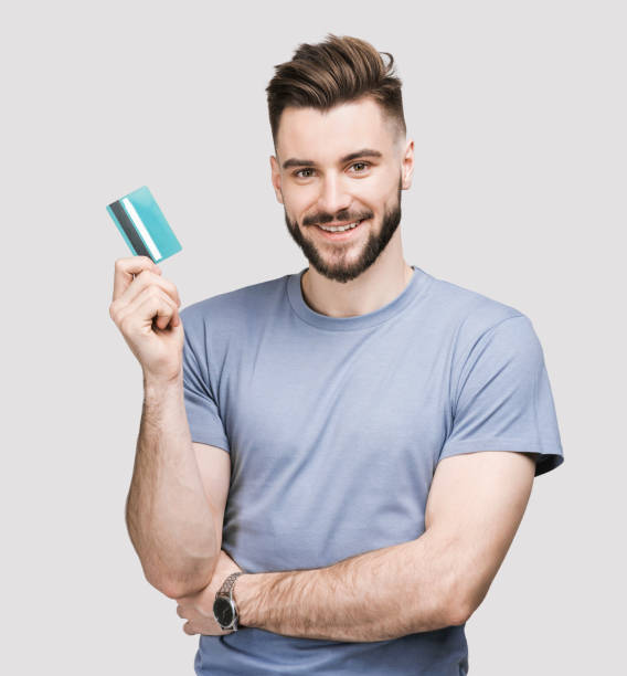 Cheerful young man showing credit card stock photo