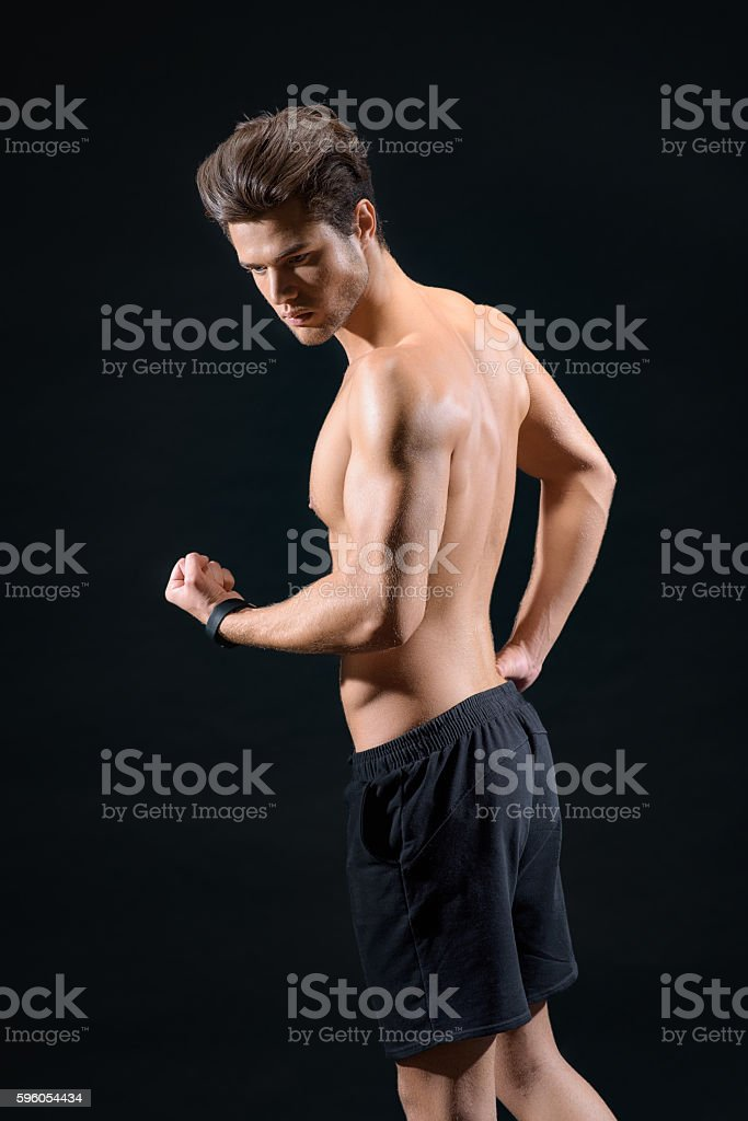 Cheerful young man showing his bicep royalty-free stock photo