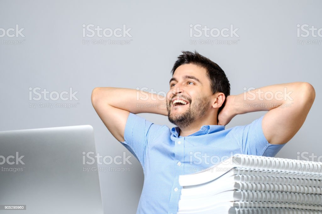 Cheerful young man sitting at the table with laptop and stretching. Isolated on gray stock photo