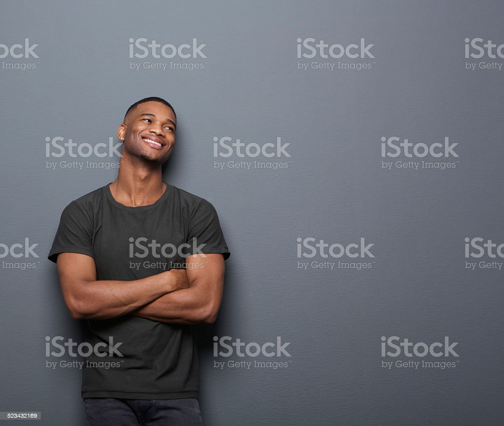 Cheerful young man smiling with arms crossed on gray background stock photo