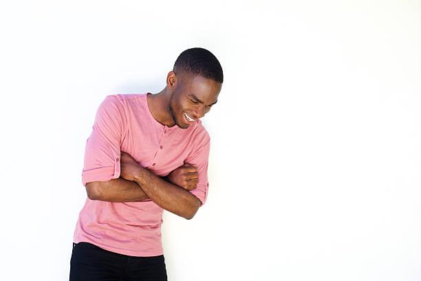 allegro giovane uomo in piedi su sfondo bianco - guardare verso il basso foto e immagini stock
