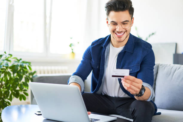 Cheerful young man using credit card and laptop to pay for shopping online stock photo
