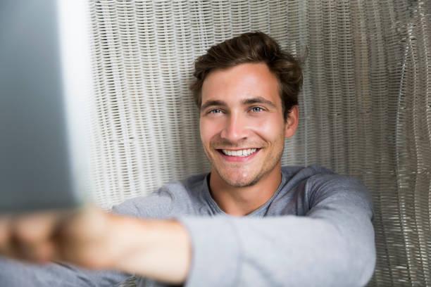 Fröhlicher junger Mann mit digitalem Tablet auf Weidenstuhl – Foto