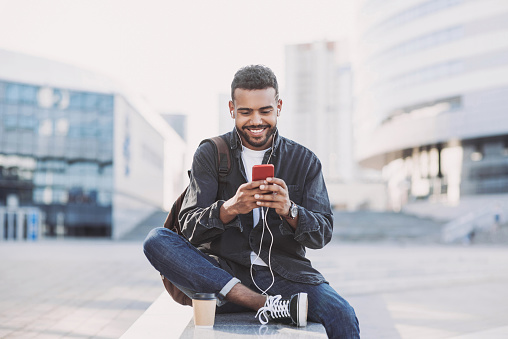 Student men using mobile phone on a city street. Freelance work, communication, business concept
