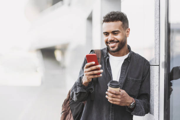 Cheerful young man using smart phone in a city stock photo