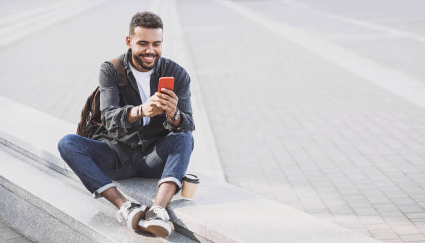 Cheerful young man using smart phone on a city street stock photo