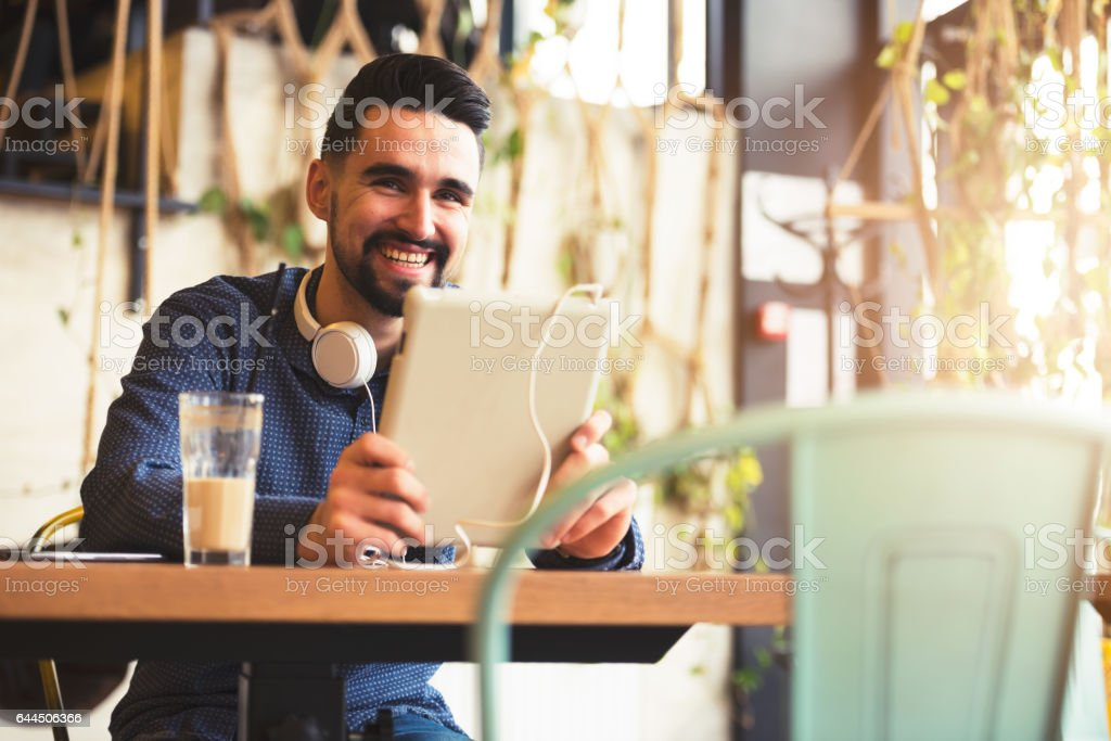 Cheerful Young Man Using Tablet with Earphones In Coffee Shop stock photo