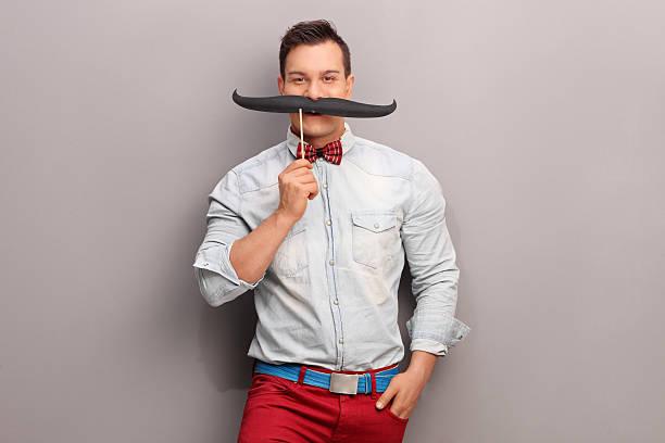 fröhlich junger mann mit einer riesigen falschen schnurrbart - riesenschnauzer stock-fotos und bilder