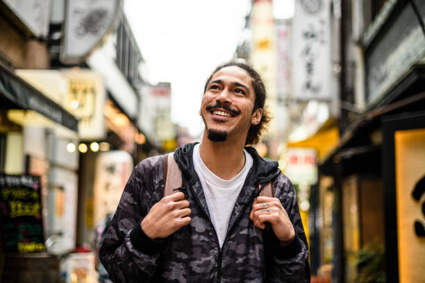 Cheerful young man with goatee looking up in city street stock photo
