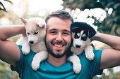 istock Cheerful Young Men Holding Two Lovely Husky Baby Puppies 841673474