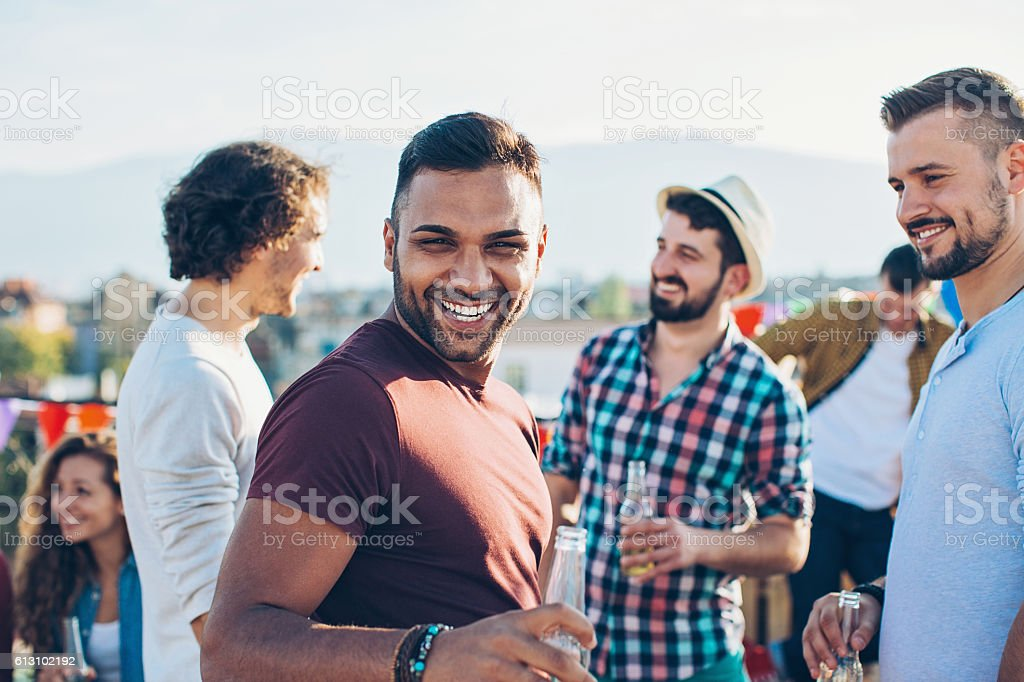 Cheerful young men on a rooftop party stock photo