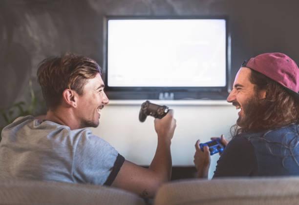 cheerful young men playing video game at home - man joystick imagens e fotografias de stock