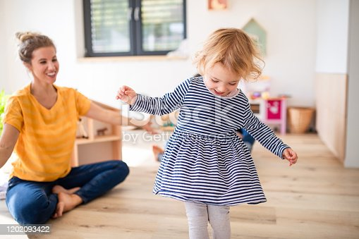 A cheerful young mother with small daughter indoors in bedroom playing.